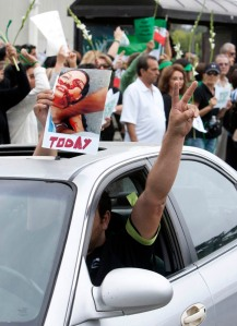 "A protestor holds a photo supposedly showing a woman named ""Neda"" who was killed Saturday in Iran."